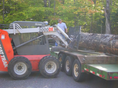 Jon and Dan maneuver the log onto the Bobcat so it can be taken back behind to LAB where students will work on it.