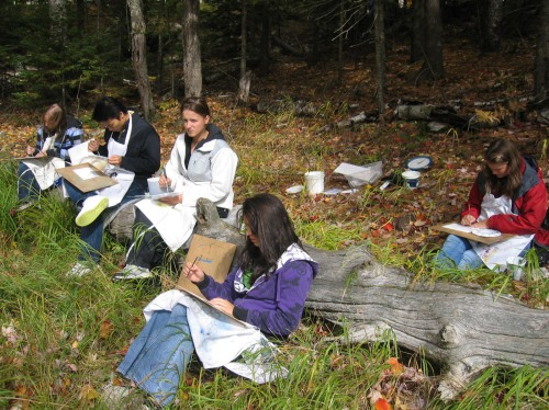 The Drawn to Nature class concentrates on the beautiful fall scene in front of them as they sit on the lakeshore.