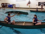 Alex and Nichole concentrate as they paddle to the center of the deep end.  In the background another canoe is submerged for a T-rescue.