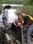 Cara, Paige, and Nathan help Kit out of waist deep mud