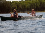 Olivia splashes Kate as they practice their canoe strokes before swamping their canoes.