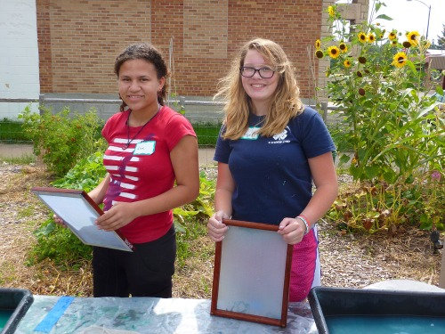 Alex and Paige pause to smile for a picture with the papermaking molds.