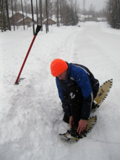Joe puts on his snowshoes.
