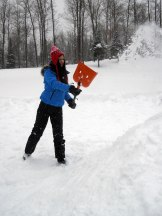 Paige shovels snow onto the mound.