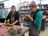Fritz rolls out clay while Erin B. examines a cup.