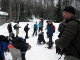 Jeff looks on while one group puts on their snowshoes and another heads into the woods.