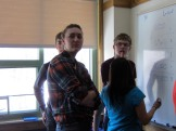 Nick, Kierra, Madi (facing away from the camera), and Grant debate their answers.