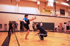 Riley practices his half-moon (meia lua) kick, while Kainoa tucks into the coconut (cocarinha) pose for defense.