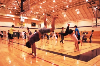 "Pardo and Max work on their ""au"", a Capoeira movement similar to a cartwheel."