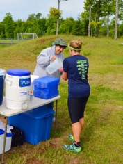 Sherrie pouring fluids for a runner at the first aid station