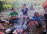 Lucas, Suzanna, and Emma around the fire